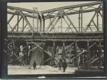 Die Trümmer der alten gesprengen Brücke im Stellgerüst der neuen Brücke