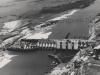 Blick gegen die Sperre und Baugrube II, von Oberwasser gesehen. Im Hintergrund die zerstörte Dienstbrücke.