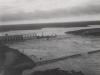 Sperre bei Hochwasser, von Unterwasser aus gesehen; Baugrube II und Fangedamm überströmt. Im Vordergrund die zerstörte Dienstbrücke.
