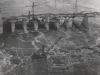 Überstömung der Baugrube II durch Hochwasser. Im Hintergrund der Kabelbahn für den Materialtransport. Im Vordergrund Derrick zur Fangedammherstellung, auf dem unterwasserseitigen Fangedamm stehend.