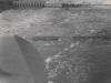 Blick auf die bisher fertiggestellten E- und Ue-Pfeiler bei Hochwasser, von Unterwasser aus gesehen. Im Vordergrund die zerstörte Dienstbrücke.