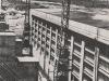 Krafthaus von der Sperrenkrone aus aufgenommen; kurz vor Abbau der Baukräne. Links im Bild ist die Krone der Windlaufpfeiler sichtbar. Die Tragkonstruktion des Krafthauses ist Eisenbeton; das Dach ist eine mit Aluminiumblechen gedeckte Stahlkonstruktion.