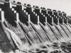 Der Überlauf ist der Bauteil, der sich als Hauptmittelteil der Sperre an das Kraftwerk anschließt. Er hat eine Länge von 160m und ist so bemessen, dass über ihm Hochwasser von bis zu 5.500 m³/sek ohne Schwierigkeit abfließen können. Normalerweise bleibt der Überlauf durch 5 m hohe, eiserne Schützen geschlossen, deren Unterkante in geschlossenem Zustande auf der Überlaufschwelle (Kote + 76,0) aufsitzt, während die Oberkante den Stauwasserspiegel + 80,0 um 1 Meter überragt. Jeder dieser Schützen wird unabhängig von den anderen durch einen eigenen 3 PS-Motor angetrieben, der imstande ist, ihn gegen den Wasserdruck in 15 Minuten zu heben oder zu senken. Daher sind diese Schützen besonders stark konstruiert und mit einem Eigengewicht von 20 Tonnen ausgerüstet worden.