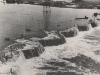 Das Hochwasser fließt über die oberstromseitige Fangedammkrone. Ein Arbeiter versucht inmitten der entfesselten Elemente etwas Verlorenes zu retten.