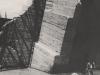 Die Anschlussfangedämme des zweiten Bauabschnittes an das linke Ufer. Hier hat das Hochwasser die Steinschüttung vollständig abgetragen und die Betonelemente der Dammanschlüsse freigelegt. Man erkennt eines der T-förmigen Betonwiderlager der letzten Uferzelle, welches vom Hochwasser von dieser abgerissen, hochgehoben und zerschmettert worden ist.